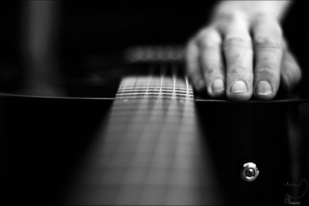 Gitarre , Sillleben. Hand auf schwarzer Gitarre, Schwarzweißfotografie